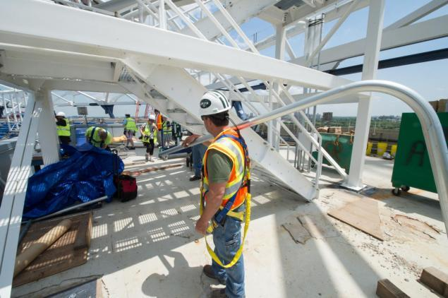 Construction workers are seen on Wednesday as the final piece of steel is put in place.